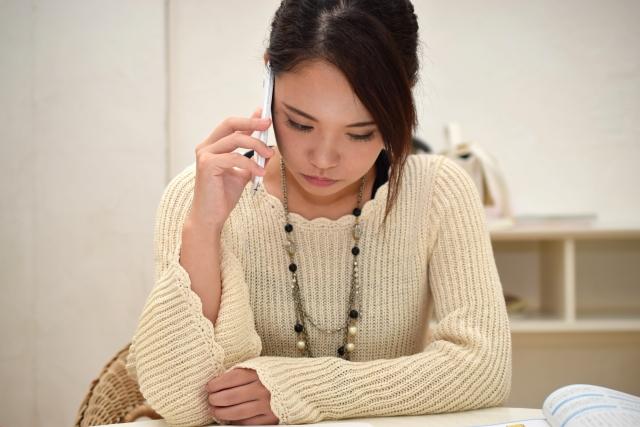 真剣に電話で略奪愛の相談をする女性のイメージ